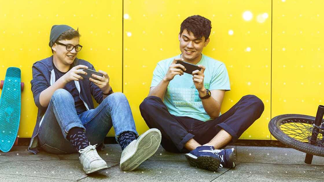 Students sitting on the pavement playing games on their phones