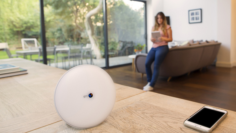 BT Whole Home Wi-Fi disc with woman using tablet in the background